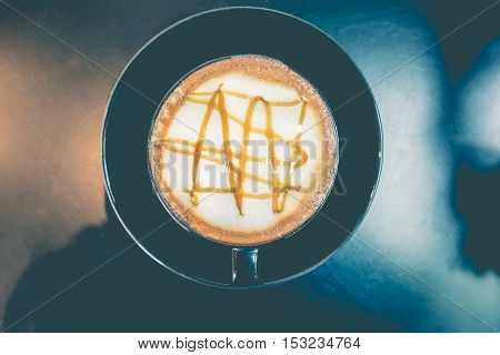 Caramel macchiato in black coffee cup on a wooden table background top view - Vintage style
