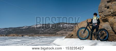 Fatbike also called fat bike or fat-tire bike - Cycling on large wheels. Traveller athlete standing on the ice of Lake Baikal, near frozen around the island. With views of the mountains and the endless ice.