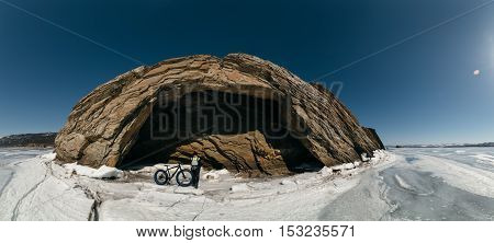Fatbike also called fat bike or fat-tire bike - Cycling on large wheels. Traveller cyclist standing on the ice of Lake Baikal, on the background of the island with a small cave gorge .