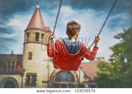 boy on a swing. child on a swing flying to the magic castle. the concept of fairy tales, dreams, imagination. the time machine