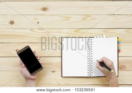 people holding and looking black screen display on smart phone with writing diary or notebook on top view wood table included clipping path on smartphone display