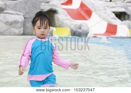 Children play in the swimming pool or water park with water slides soft focus
