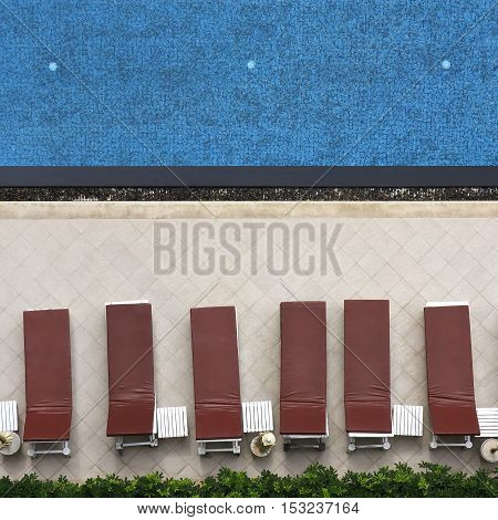 swimming pool with long chairs set in the hotel on top view and square shape