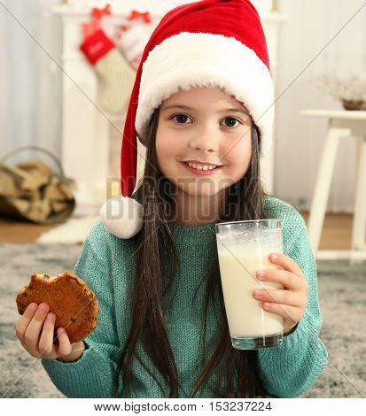 Cute little girl in Santa hat drinking milk and eating delicious cookie at home