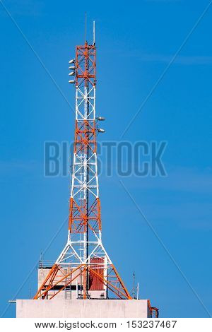 The telecommunication tower close-up with blue sky background