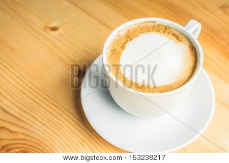 Coffee cup and saucer on wooden table at coffee shop. Top view