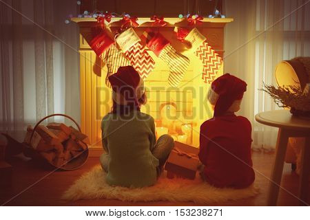 Cute little kids in Santa hats sitting on rug near fireplace at home