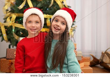 Cute little kids in Santa hats at home