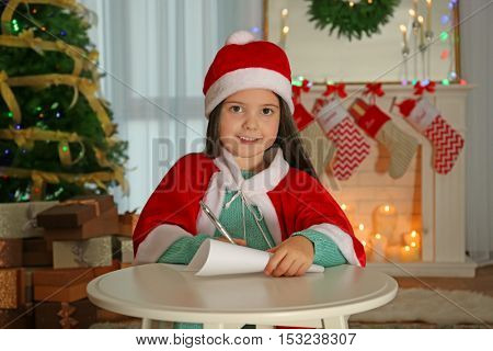 Cute little girl writing letter to Santa Claus at table