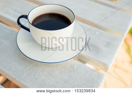 Coffee cup and saucer on wooden table in cafe. Top view