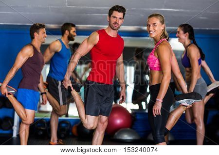 Happy athletes standing on one leg in gym