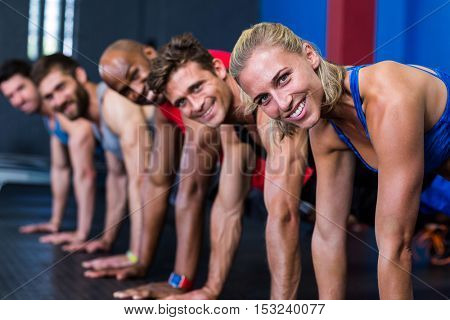Portrait of smiling people doing push-ups while exercising in gym