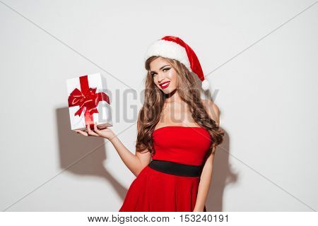 Happy pretty woman in red santa claus dress and hat holding gift box isolated on the white background
