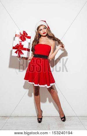 Attractive brunette woman standing with stack of gift boxes isolated on the white background