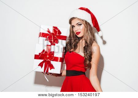Happy pretty woman in red santa claus dress and hat holding gift boxes isolated on the white background