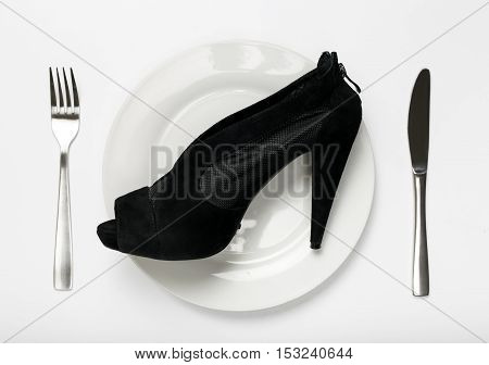 Women shoes on plate on a white background. The concept of food for fashionistas