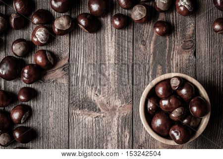 Pile of horse chestnuts in a bamboo bowl on wooden table