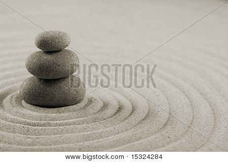 Three stones on raked sand