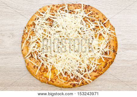 Round whole pizza with freshly grated mozzarella cheese on top