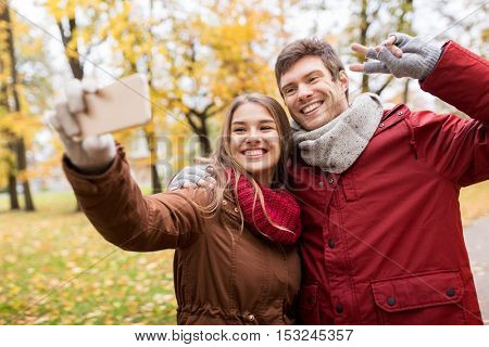 love, technology, relationship, family and people concept - smiling couple taking selfie by smartphone in autumn park