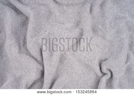 close up grey knitted pullover background. Top view.