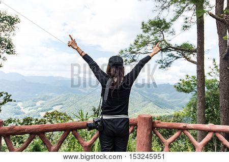 Hipster Girl with backpack enjoying the sunset on top of a mountain map. Travel in a mockup background valley landscape sunlight travel.