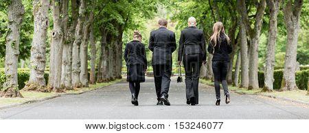 Family walking down alley at graveyard