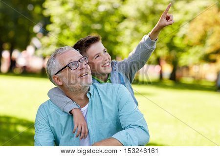 family, generation, relations and people concept - happy grandfather and grandson pointing finger up to something at summer park