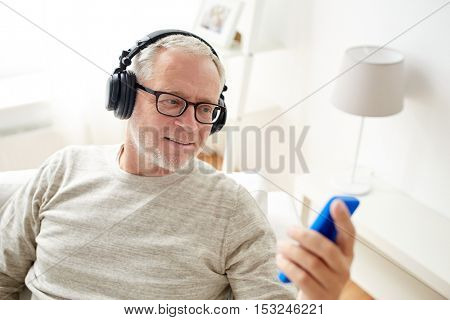 technology, people, lifestyle and distance learning concept - happy senior man with smartphone and headphones listening to music at home