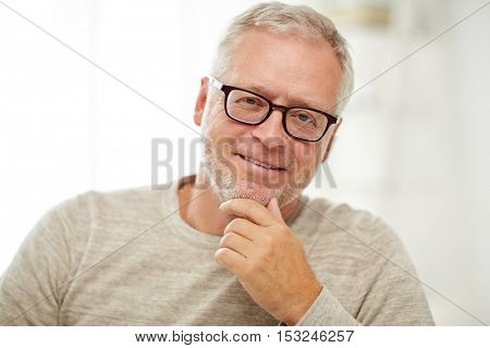 old age, vision and people concept - close up of smiling senior man in glasses thinking