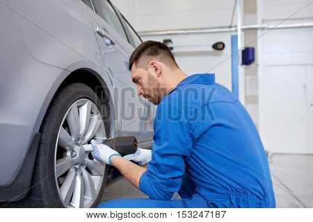 car service, repair, maintenance and people concept - auto mechanic man with electric screwdriver changing tire at workshop