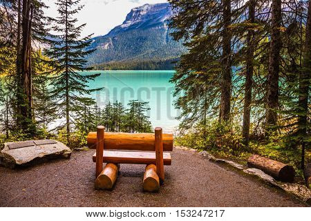 The concept of eco-tourism and adventure tourism. Camping at Lake Emerald. Wooden bench on the lake shore