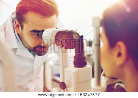 health care, medicine, people, eyesight and technology concept - optometrist with non contact tonometer checking patient intraocular pressure at eye clinic or optics store