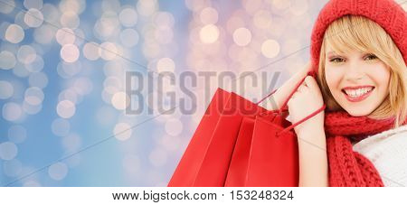 winter holidays, christmas and people concept - smiling young woman in hat and scarf with red shopping bags over lights background