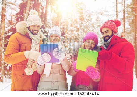 technology, season, friendship and people concept - group of smiling men and women with tablet pc computers in winter forest