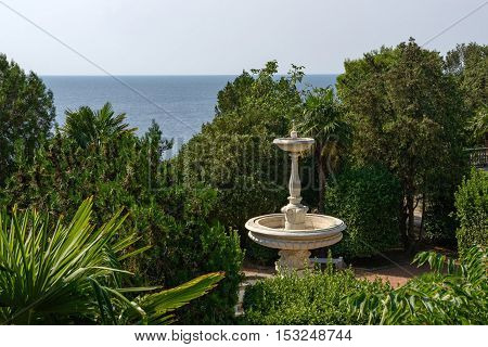 Classic Fountain Among Trees And Bushes In Park Near Sea.