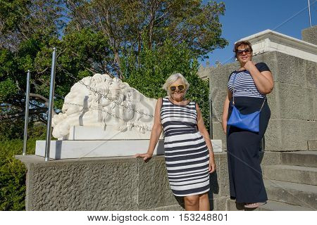 Women Are Standing On Stairs Near Lion Sculpture In Park.