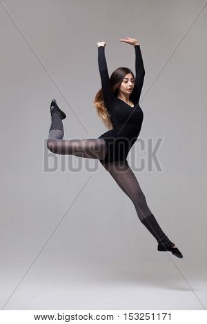 young beautiful woman dancer in black swimsuit jumping on a grey studio background
