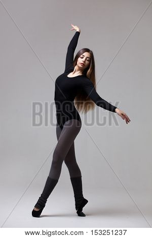 young beautiful woman dancer in black swimsuit posing on a grey studio background