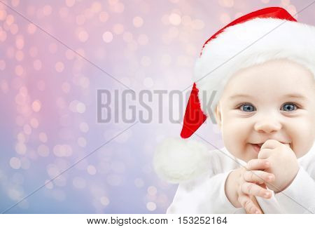 christmas, babyhood, childhood and people concept - happy baby in santa hat over rose quartz and serenity lights background
