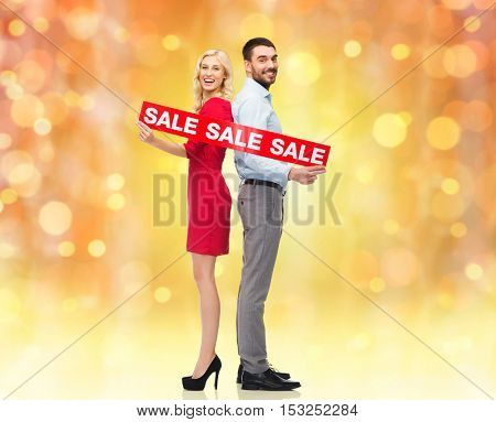 people, christmas, sale, discount and holidays concept - happy couple with red sale sign standing back to back over lights background