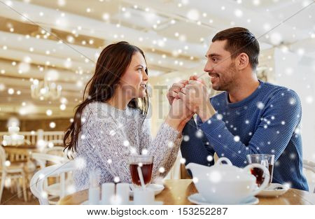 people, love, romance and dating concept - happy couple drinking tea and holding hands at cafe or restaurant
