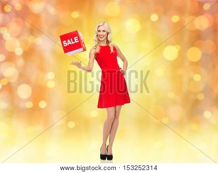 people, christmas, shopping, discount and holidays concept - smiling woman in red dress holding cardboard box with sale sign over lights background