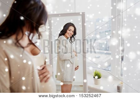 pregnancy, winter, christmas, people and expectation concept - happy pregnant woman looking to mirror at home over snow