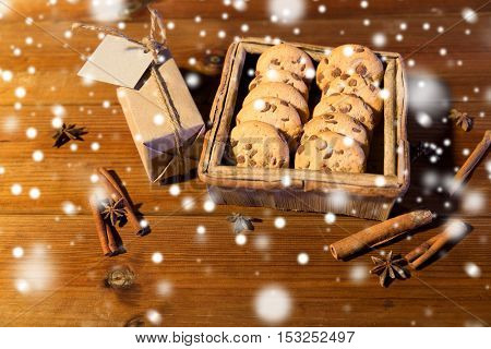 christmas, baking, holidays and food concept - close up of oat cookies in wooden box, gift with blank greeting card or note and cinnamon on table