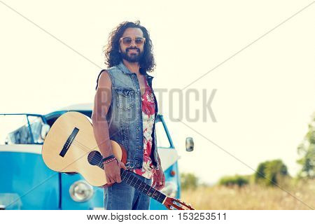 nature, summer, youth culture and people concept - young hippie man playing guitar and singing over minivan car outdoors