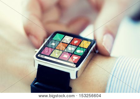 business, technology, communication, multimedia and people concept - close up of woman hands setting smart watch with application icons on screen
