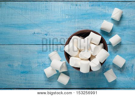 Fluffy white marshmallow in ceramic bowl on blue wooden table. Top view