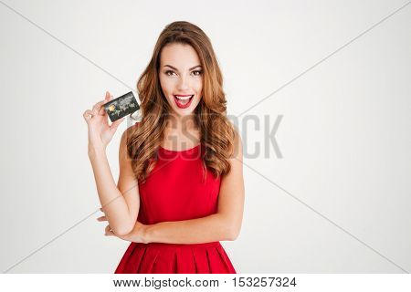Cheerful young woman in red dress holding bank card isolated on a white background