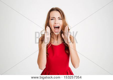 Portrait of a brunette pretty woman in red christmas dress shouting at camera isolated on a white background